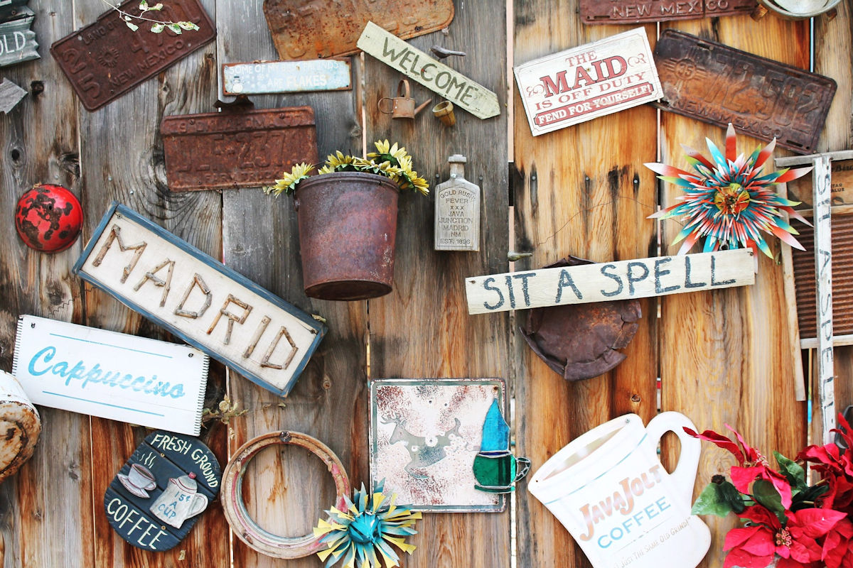 Eclectic signs and primitives on a coffee shop wall.